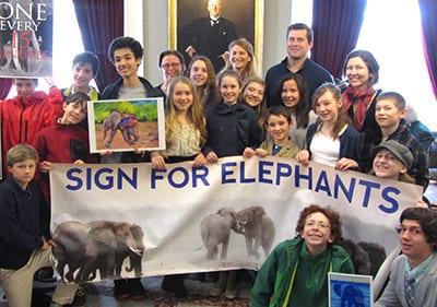 Taegan and Legislators Holding Sign for Elephants Banner