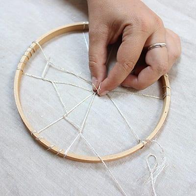 Hand holding the string to weaver around the dreamweaver craft