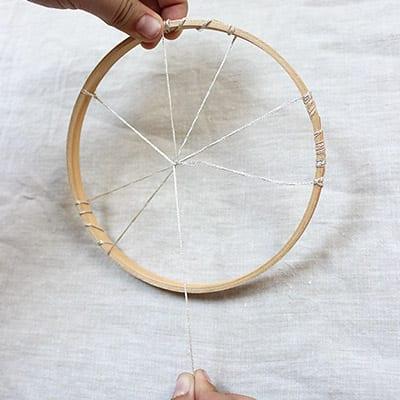 Hands holding dreamweaver weaving string around to create craft