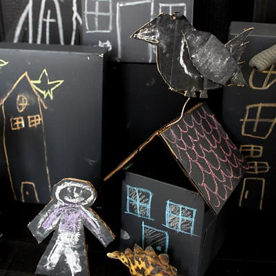 Closeup of cardboard town house with cardboard crow on top