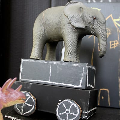Closeup of a cardboard car with an elephant toy on top!
