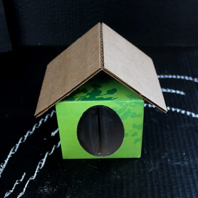 Closeup of cardboard house made of tissue box and two pieces of cardboard for a roof