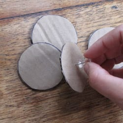 Pushing a pin through cardboard wheels
