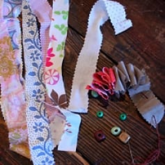Gathering materials including fabric strips, needles, thread, beads, and scissors