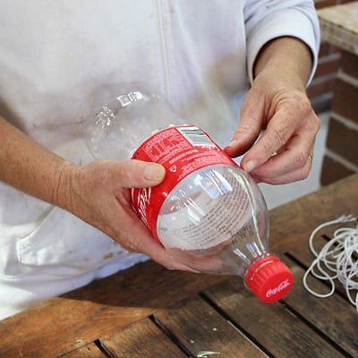 Getting ready to peel label off of empty plastic cola bottle