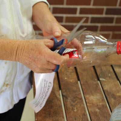 Peeling the label off of an empty plastic soda bottle