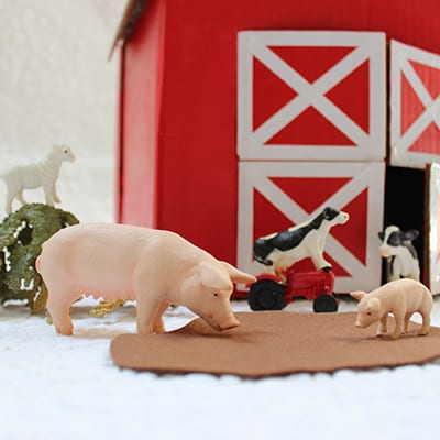 """Pigs figurines playing in foam """"mud"""" with cow and sheep figurines in the background in front of crafted red barn."""
