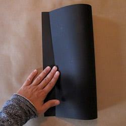 Folding black card stock paper in half vertically.
