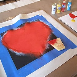 Heart stencil fully painted in red on the pillow cover.