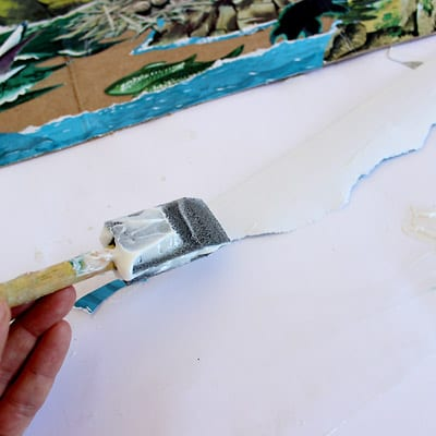 A foam brush applying modge podge to the backside of an illustration from The Little Island.