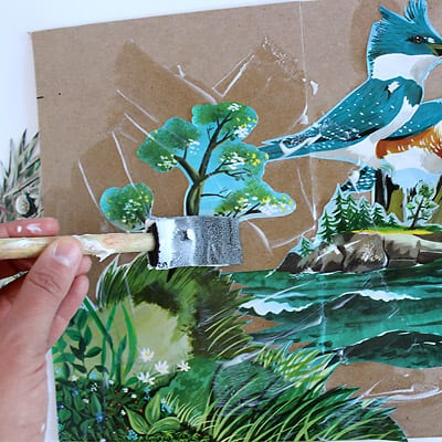An image detailing using a foam brush to modge podge The Little Island illustrations to the medium weight craft paper.