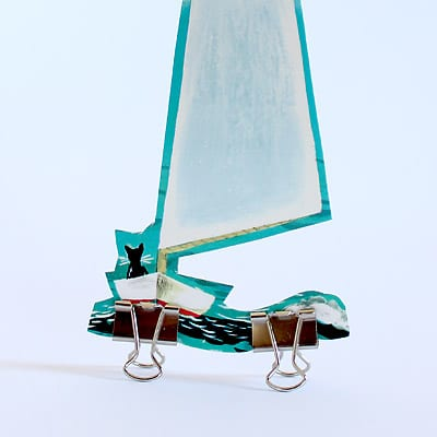 Boat illustration from The Little Island book being propped up by two binder clips.