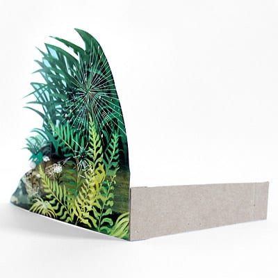 Image of foliage illustration being propped up by folded medium weight craft paper.