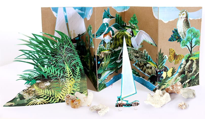 Illustrations of animals and nature from the book The Little Island pasted on medium weight craft paper. In front of the scene sits an illustration of foliage and a boat being held up by small binder clips and small pieces of coral.