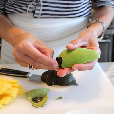 Woman removing the skin from a quarter piece of an avocado.